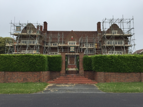 View of the front of the house fully scaffolded.